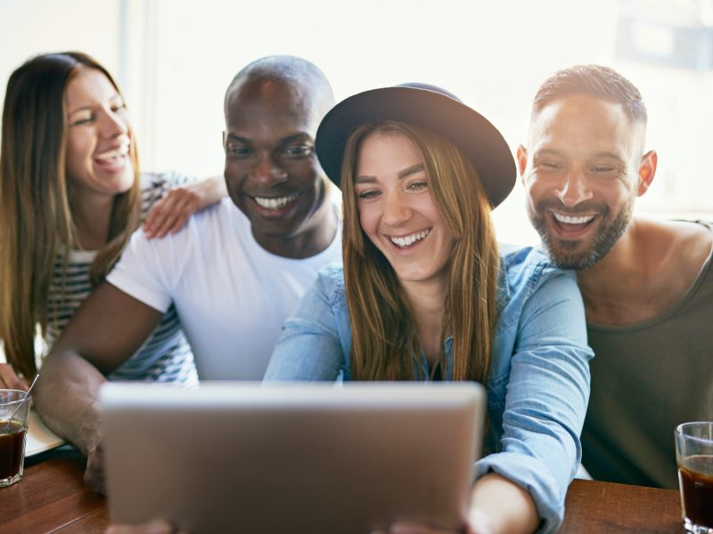 Cheerful group of young co-workers sharing tablet