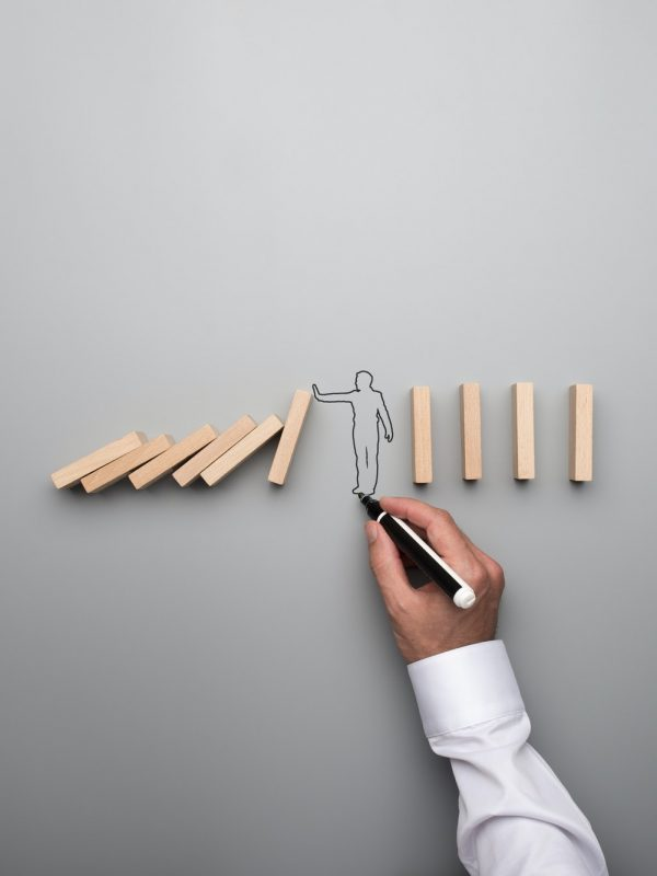 Man drawing the outline of a businessman stopping the domino eff
